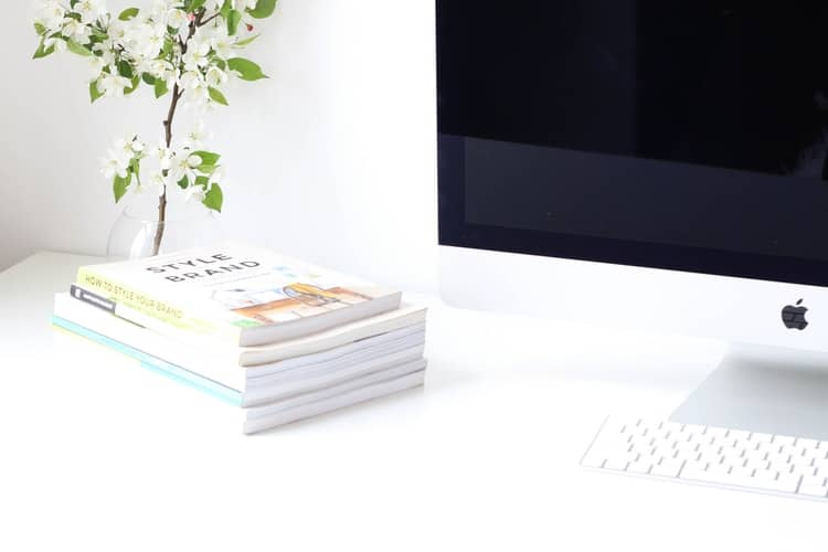 white blogging desktop with computer and books