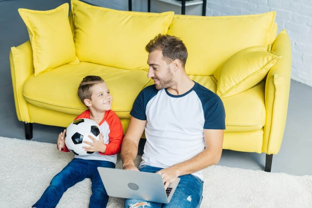 a dad working online with laptop and son with football