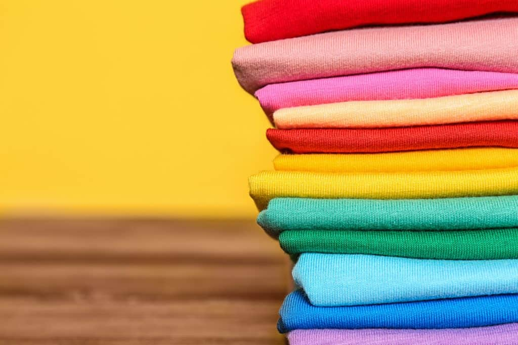 Stack of colorful t-shirts - make money selling t shirts online on Amazon