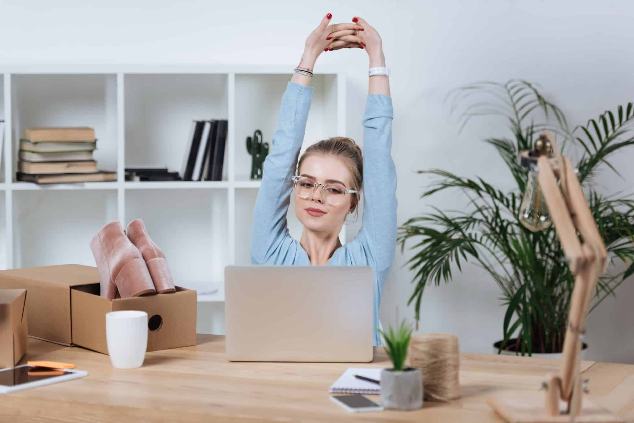 work from home jobs for mums - a woman stretching at her computer with a box of shoes ready to ship and sell online