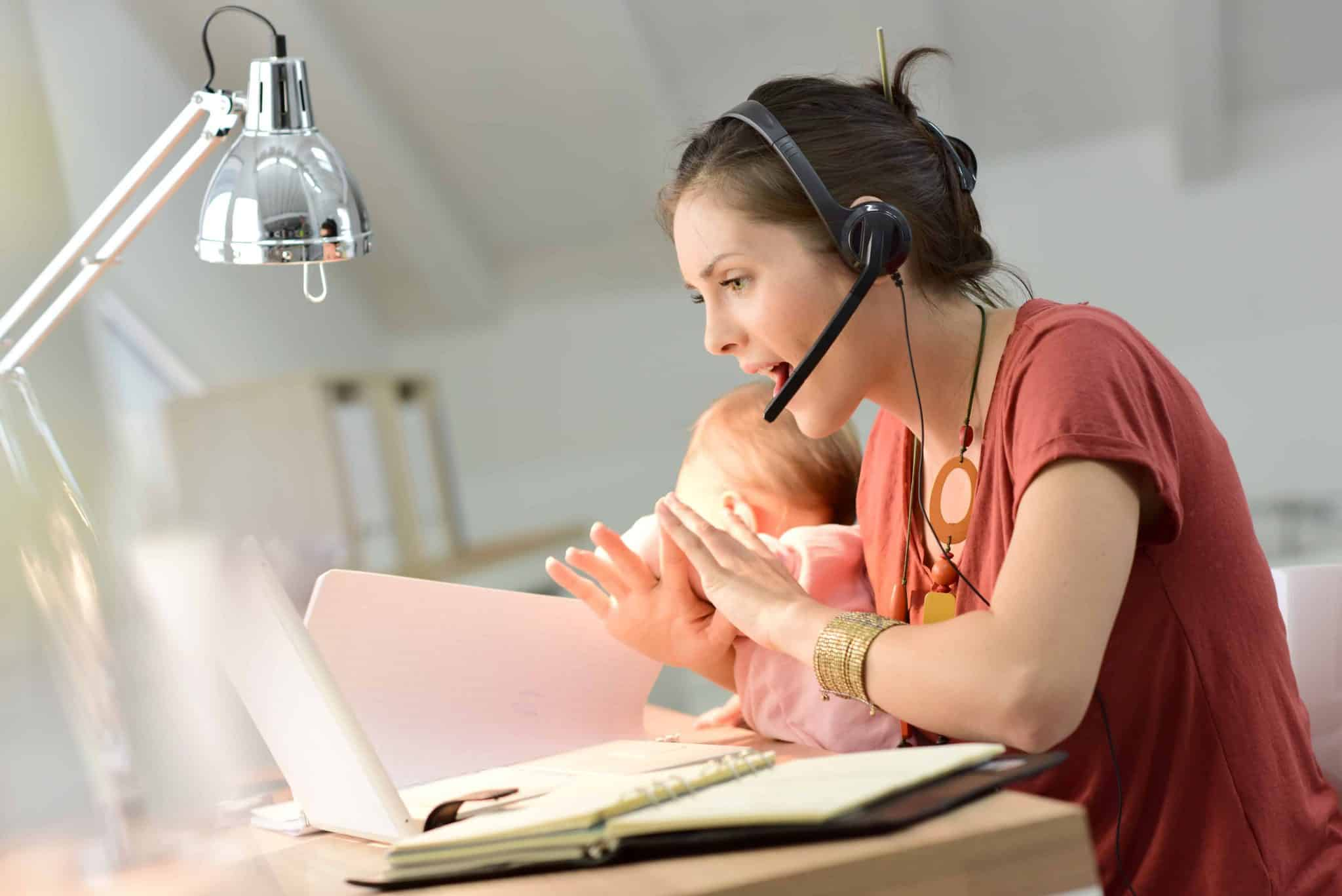 work from home jobs for mums - a woman teaching English online wearing a headset and holding a baby