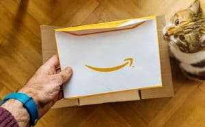 a man's hand holding an Amazon envelope with a cat watching