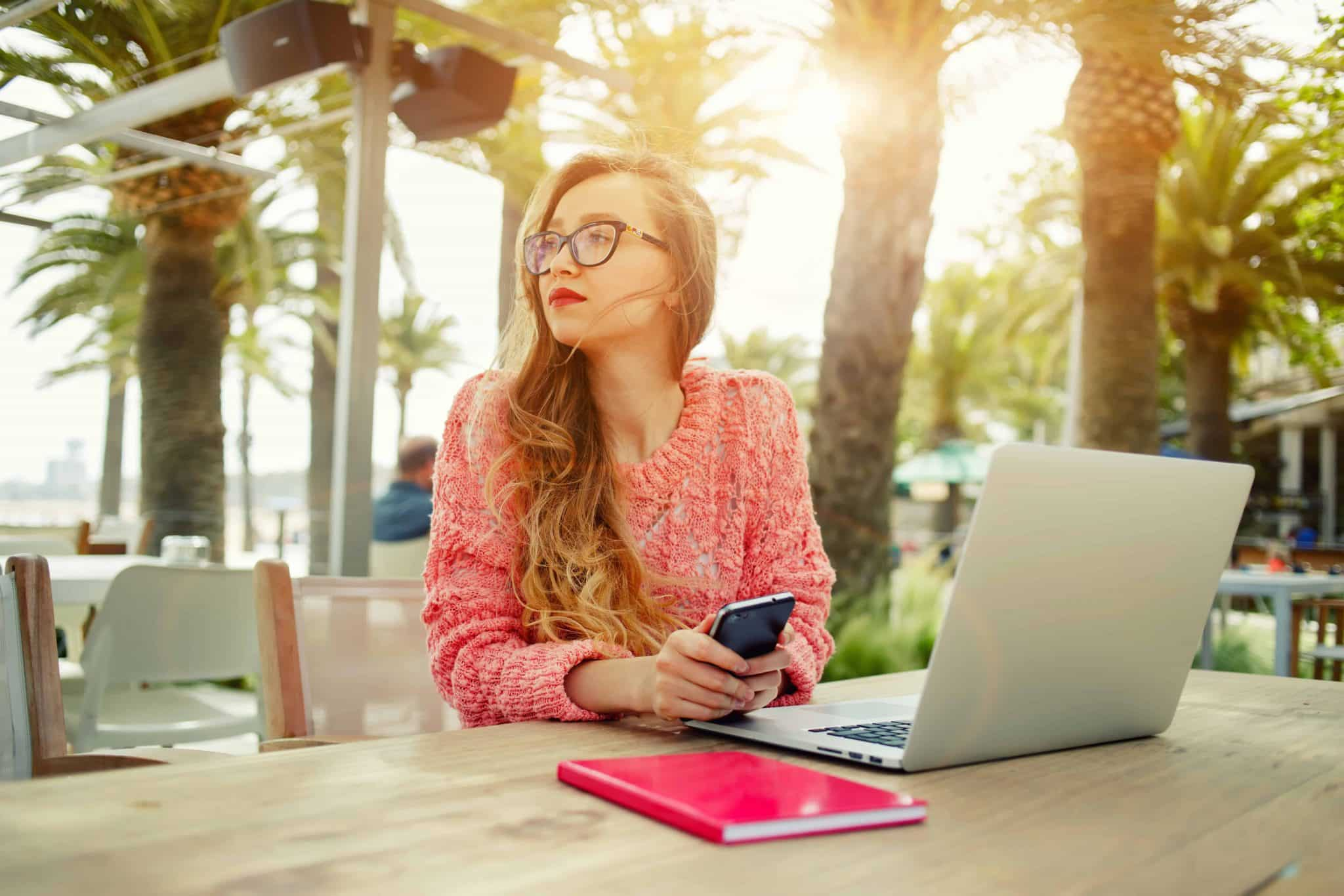 Blogger in pink working outside. Blogging is a fantastic work from home idea and you can start for free!