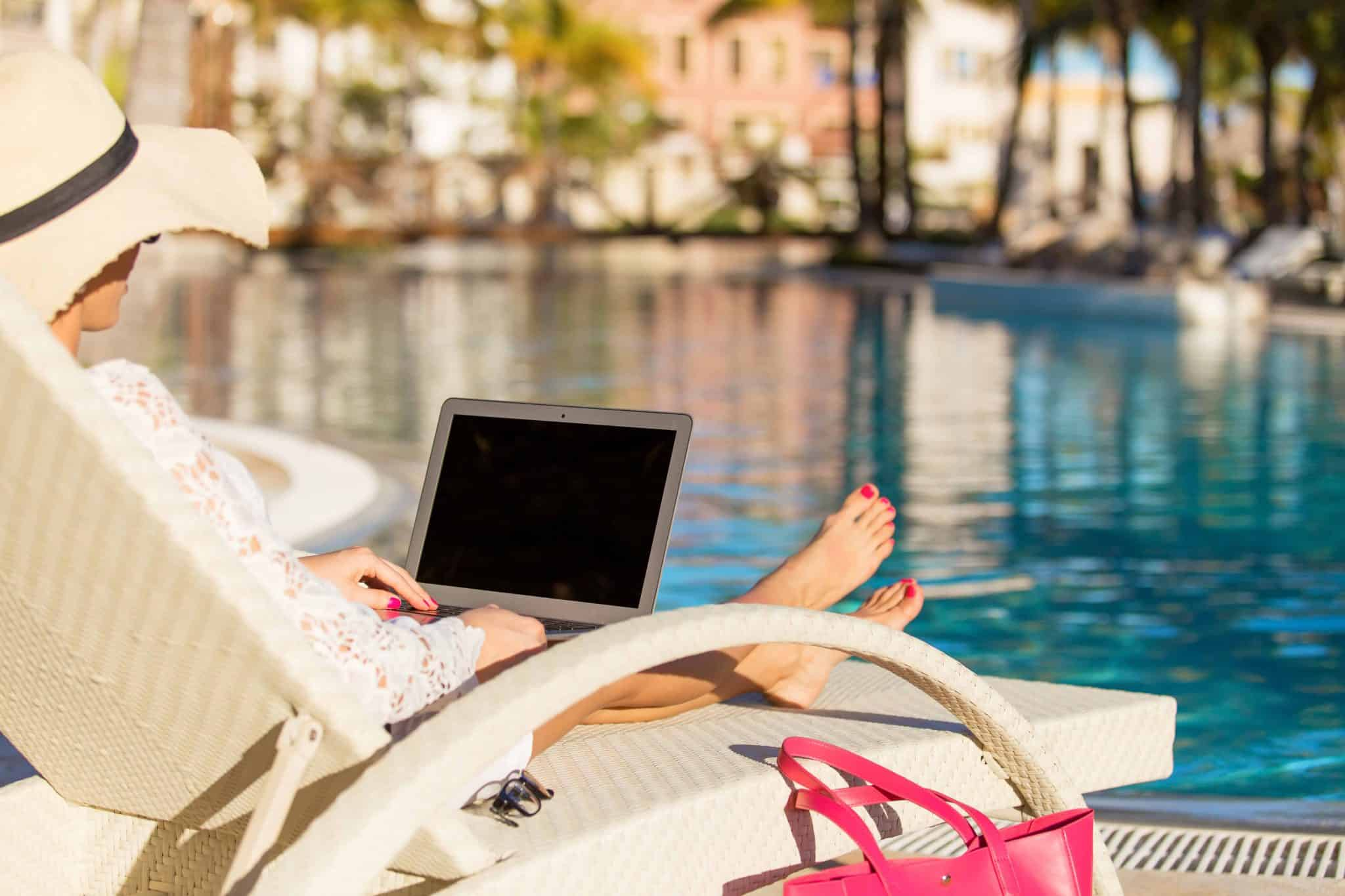 Woman lying by a pool blogging on her laptop