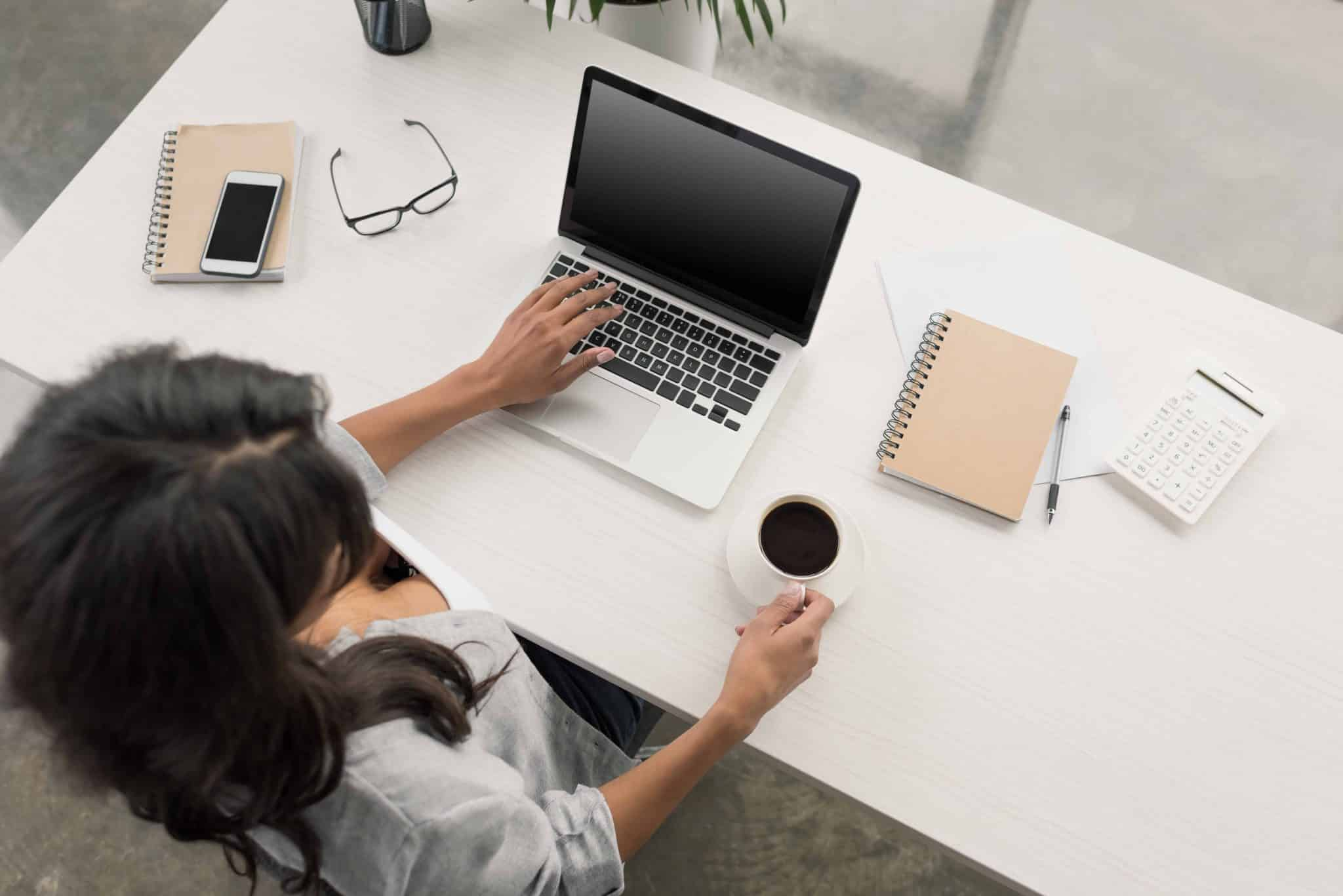 a blogger at her desk with laptop and coffee