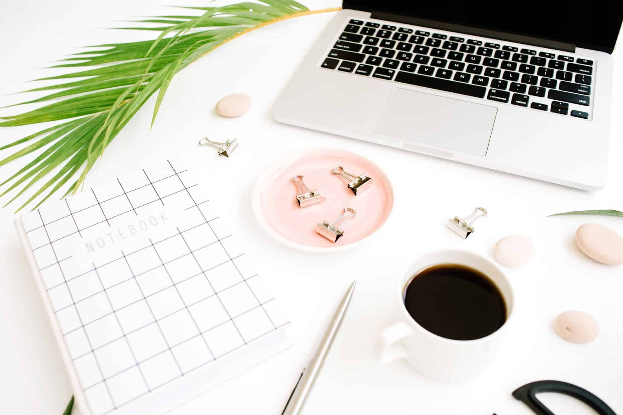 a blogger workspace flat lay with laptop, coffee and notebook