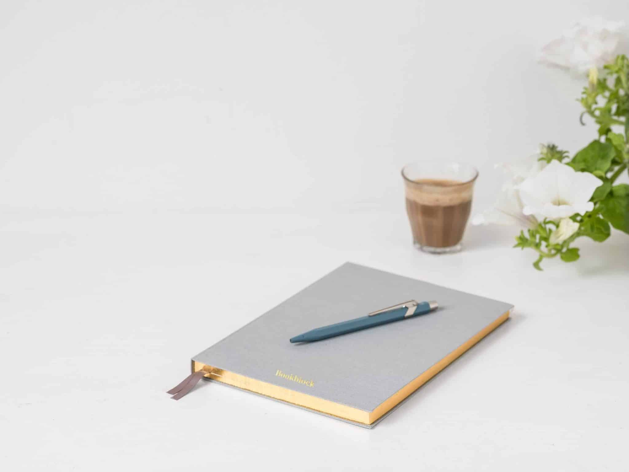 a desktop image with notebook, pen, coffee and flowers