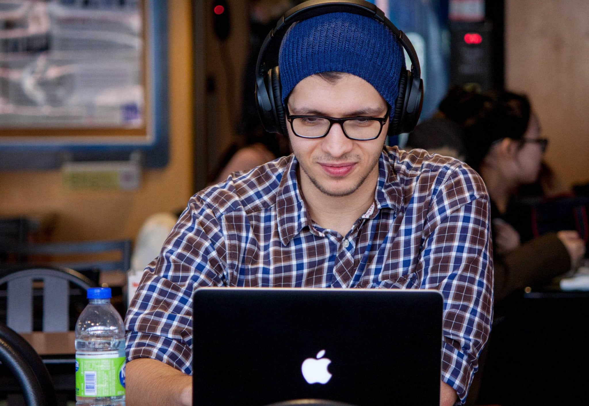 male student studying at his laptop. Find out how to study online for a free degree course!