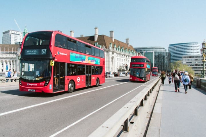 London buses on a street. One way to make money on Airbnb without owning a property is by offering guided tours of your city on Airbnb Experiences.