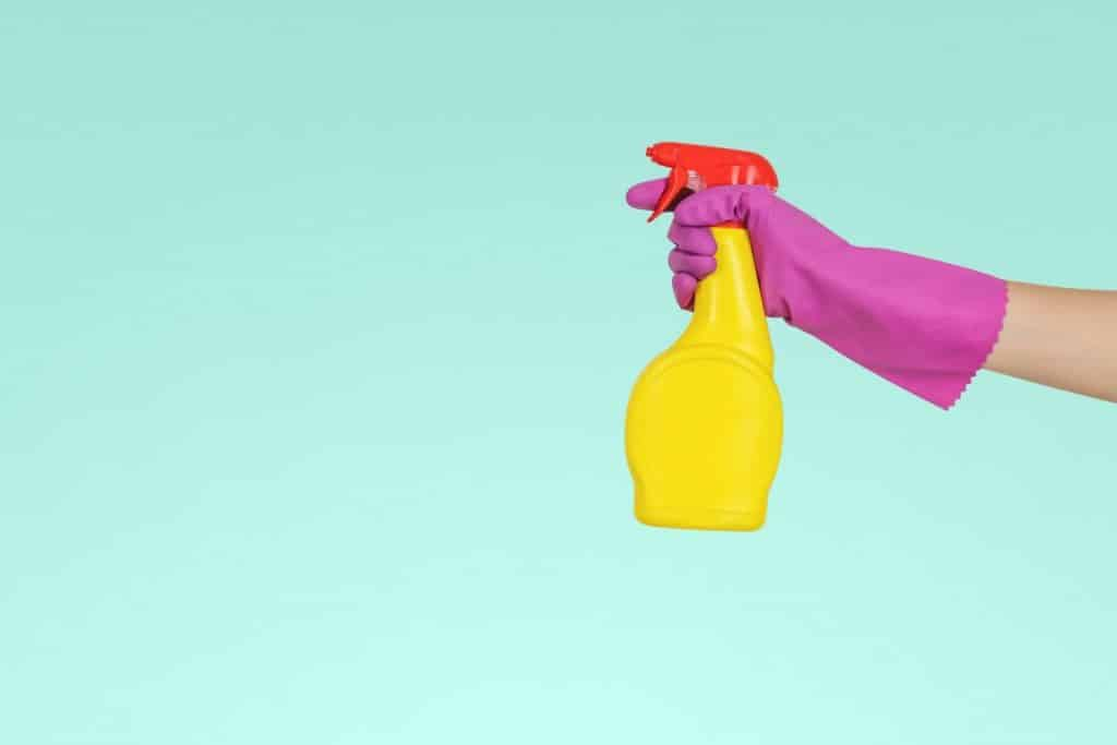 A hand in rubber glove holding a cleaning spray. You can make money from the Airbnb boom by offering specialised Airbnb cleaning services.