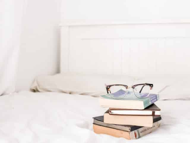 pile of books on a bed