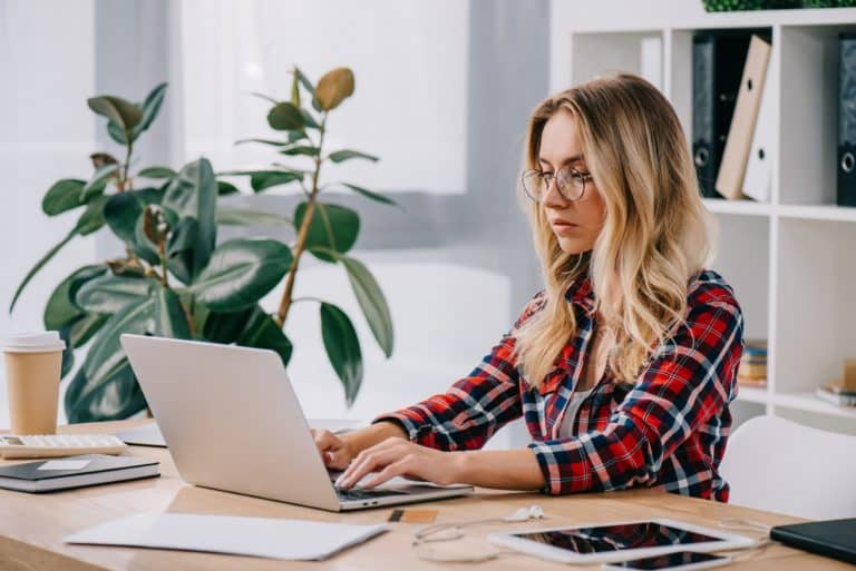 how to earn extra money in the UK - a woman works at her laptop
