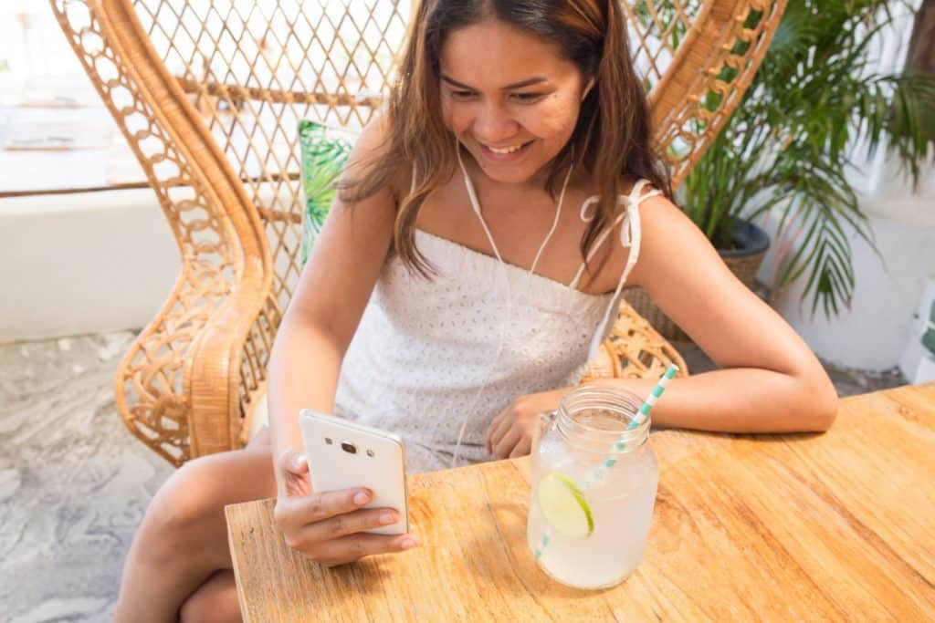 smiling girl looking at her phone with a drink