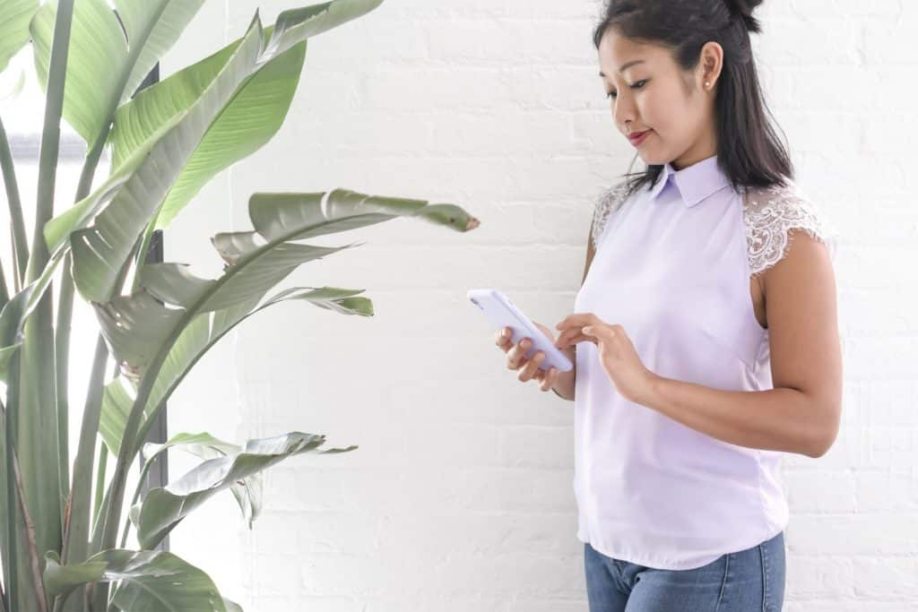 fashionable girl looking at her phone against a white brick wall