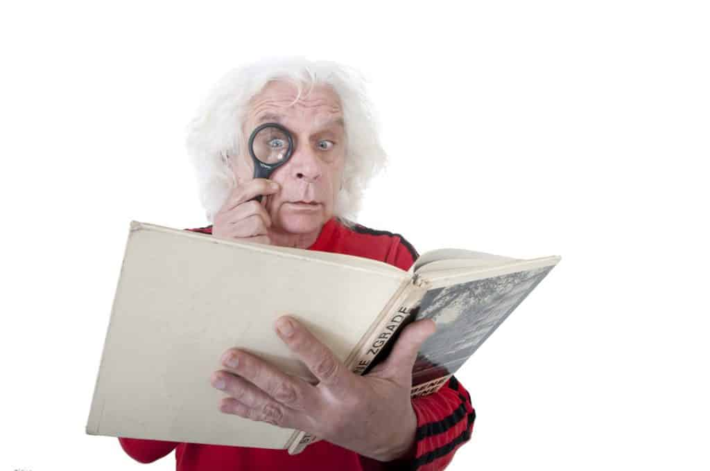 a man reading a book with a magnifying glass