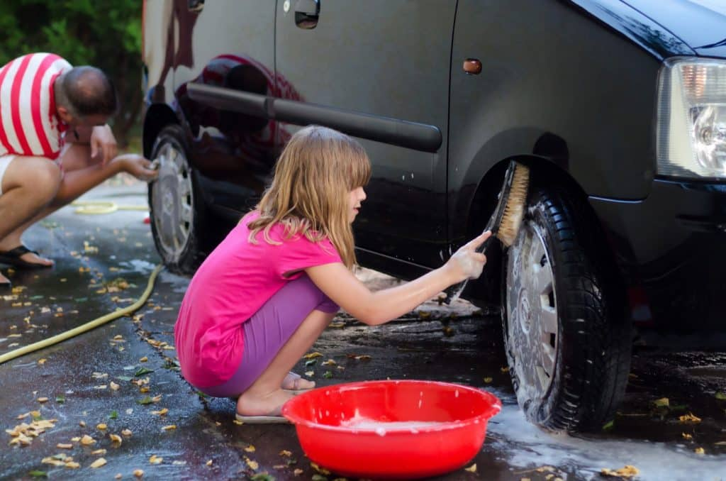 a young girl washing a car for money
