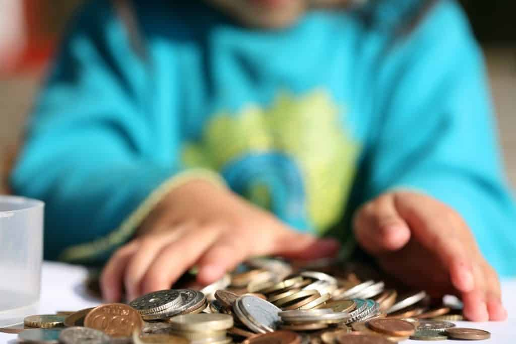 a child counting their pocket money in coins