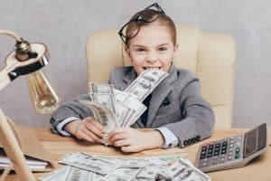 how to make money as a kid - a child dressed as a businessperson with lots of cash