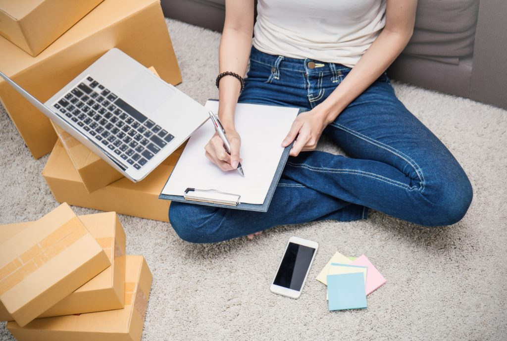 An Amazon FBA seller with boxes and laptop