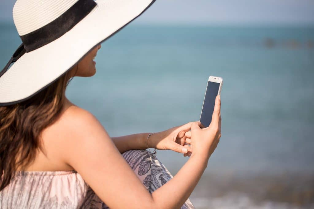 woman on her phone by the sea- you can get paid to use your phone to make extra money without a job!