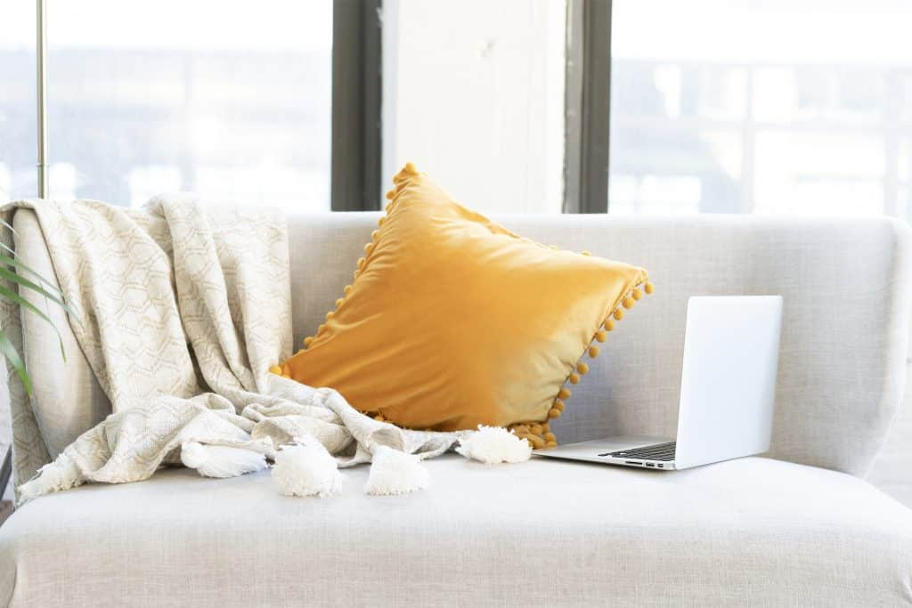 a grey sofa with yellow cushion - this could be your office if you get an online job from home!