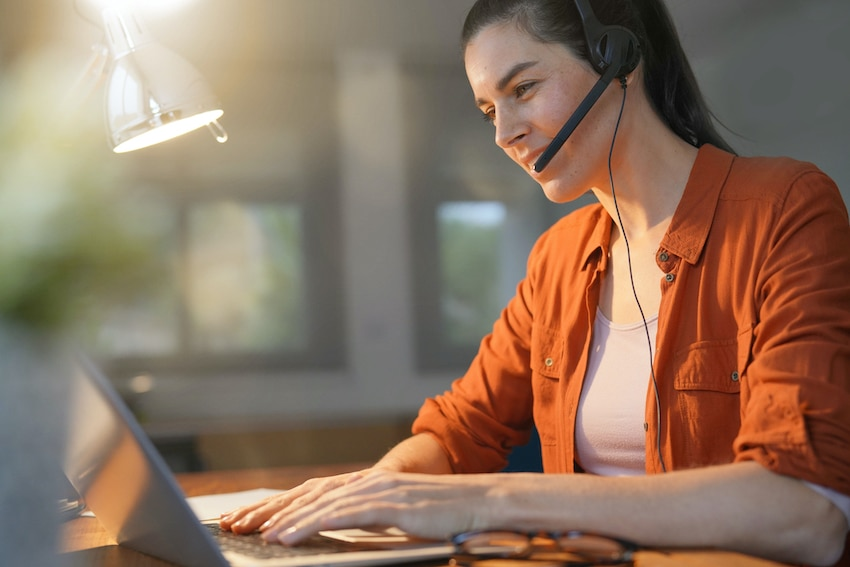 a woman wearing a headset doing a customer service job to make extra cash