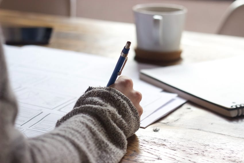 A hand holding a pen writing on some papers with coffee on desk. earn extra money marking exams
