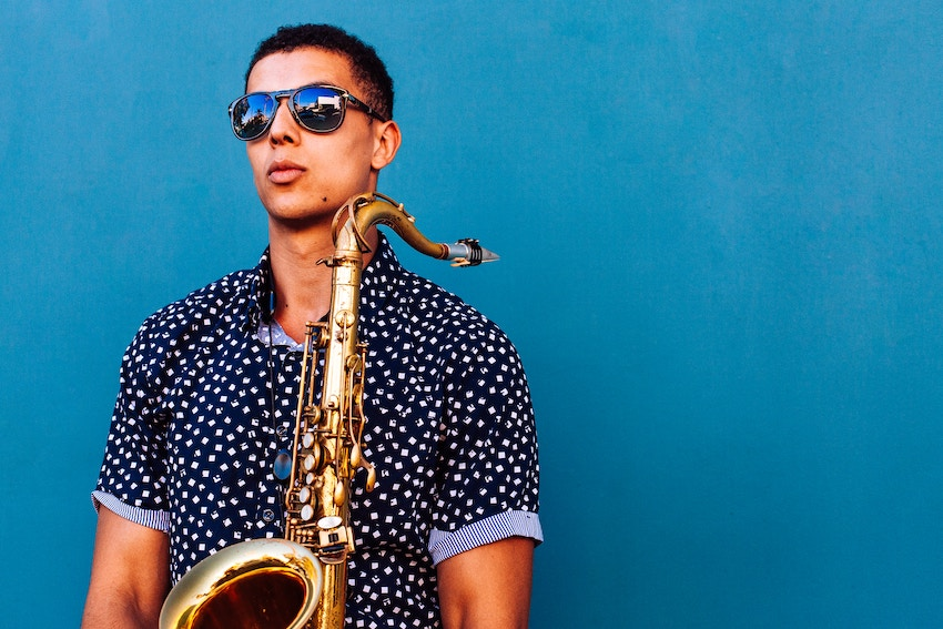 a street musician holding a saxophone against a blue background.