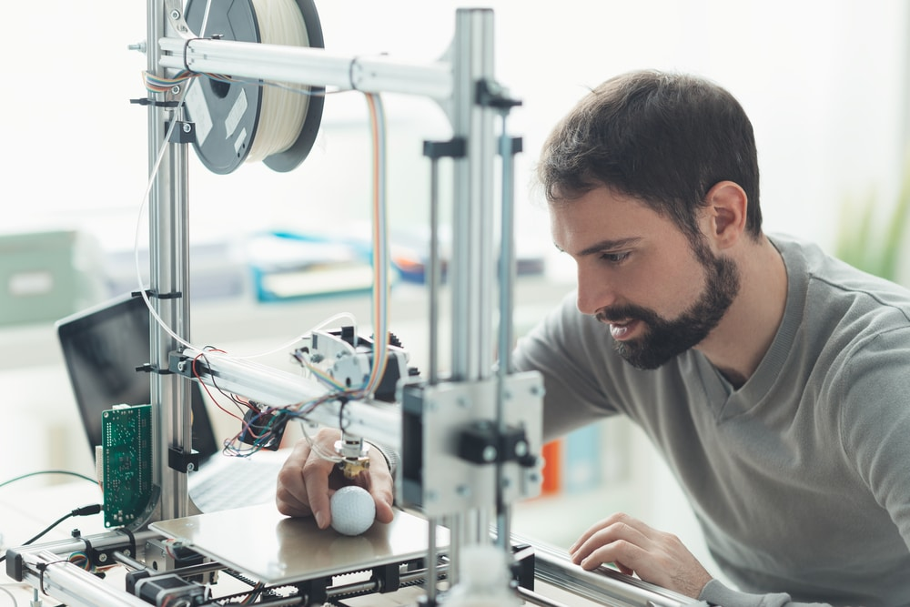 A man using a 3D printer at home. There's a start up cost, but you don't need special skills and you can use your 3D printer to make money.