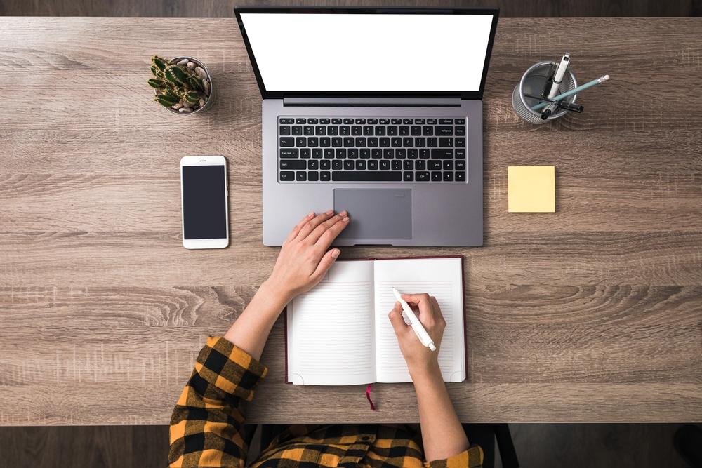 a flat lay showing the desk of a freelance writer working online with a notepad and laptop