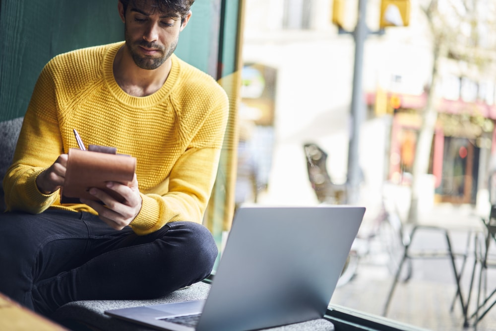 a man in yellow jumper working on tablet with laptop open