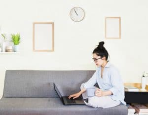 A woman sitting on her sofa using her laptop