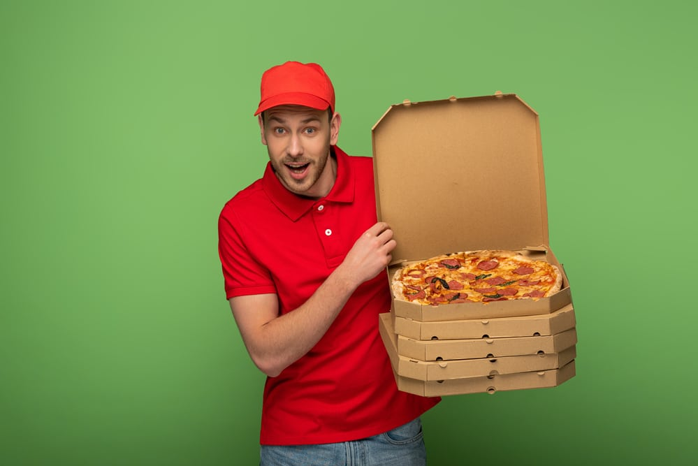a happy pizza delivery man in red with a stack of pizzas, showing an open pizza box