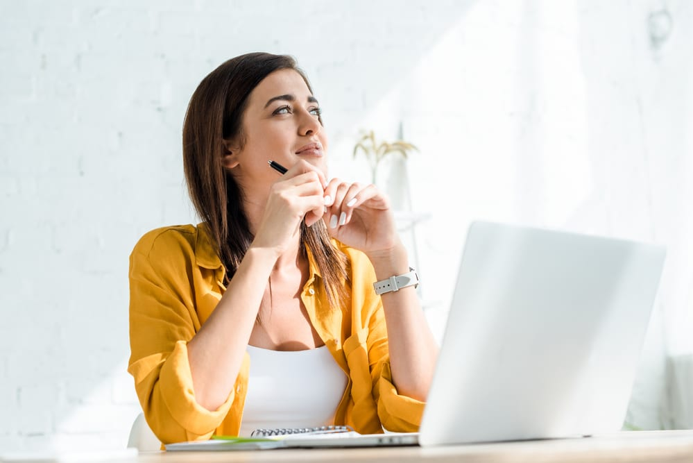 a freelance woman sitting at her desk with a laptop in front of her and a pen in her hand, thinking