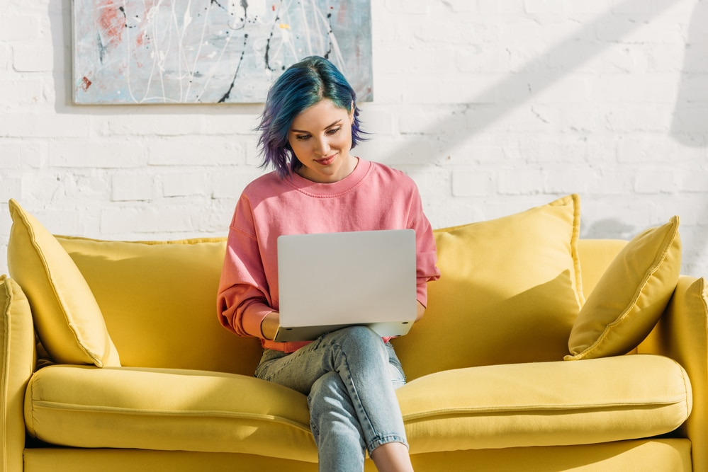 a woman with blue hair on a yellow sofa working on gpt sites on her laptop