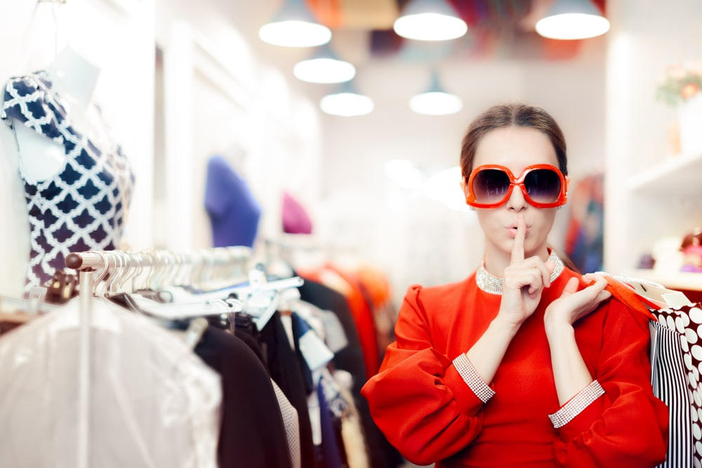 a mystery shopper wearing big sunglasses and holding a finger to her lips, in a clothes shop