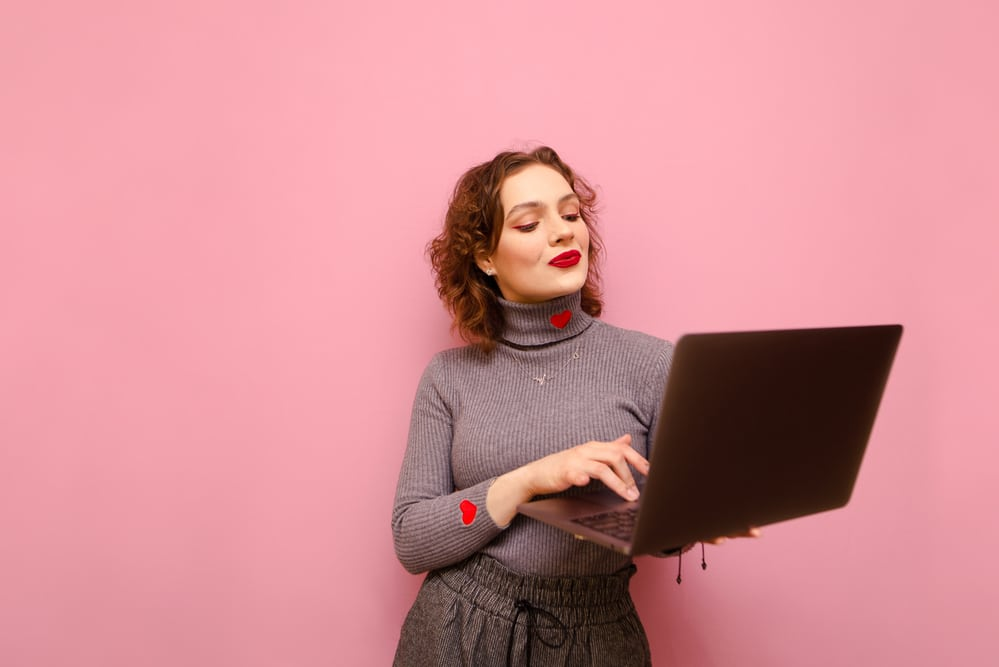 side hustle uk: a woman in grey smiling at her laptop against a pink background