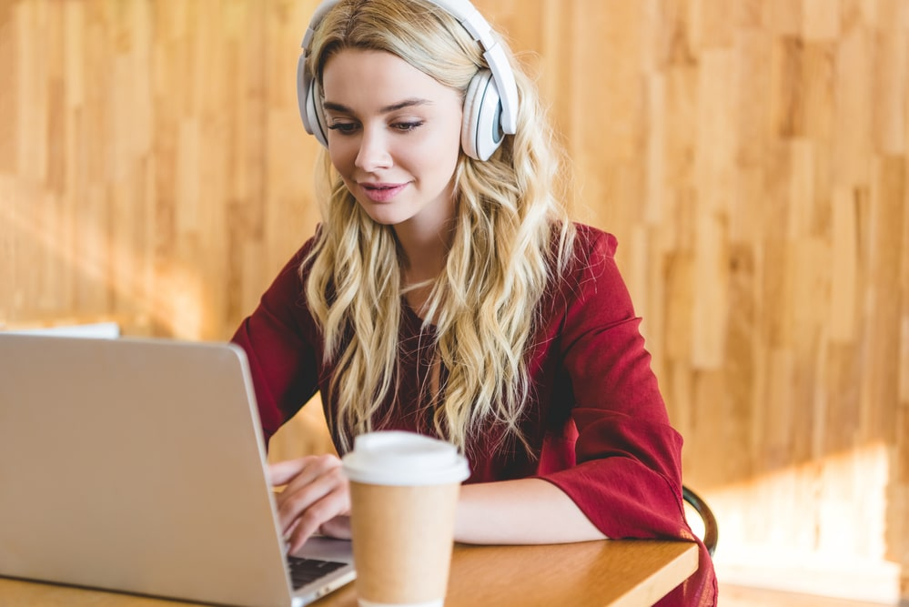 A transcriber working with headphones, laptop and coffee