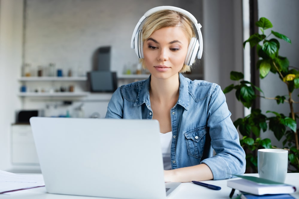 a woman in blue denim shirt sitting in front of her laptop, wearing headphones