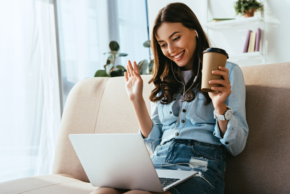 a woman chatting online holding a coffee