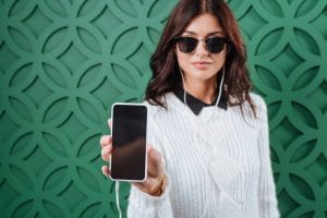 woman in sunglasses holding out mobile phone; green background