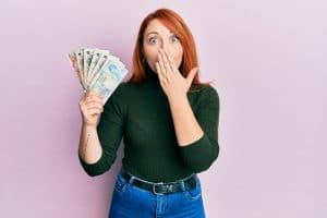 a woman holding a handful of Uk pound sterling notes and covering her mouth in surprise