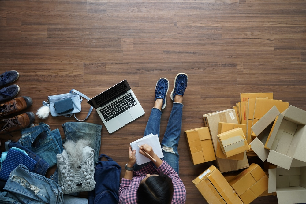 A woman sits with a laptop and notepad, surrounded by piles of shipping boxes, working on her Amazon business.