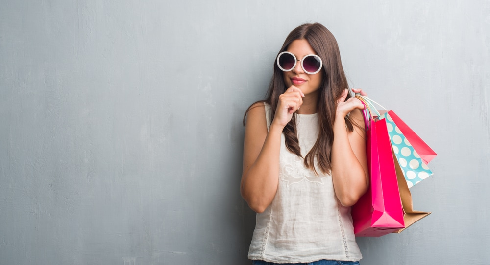 a young brunette mystery shopper holding shopping bags and wearing sunglasses