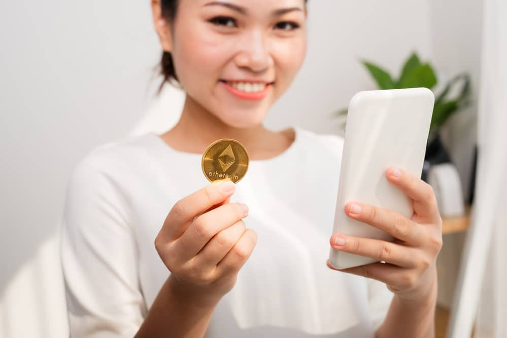 woman holding up an Ethereum crypto coin and a smart phone